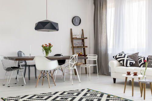 un tavolo con delle sedie bianche e un divano bianco in un ampio locale