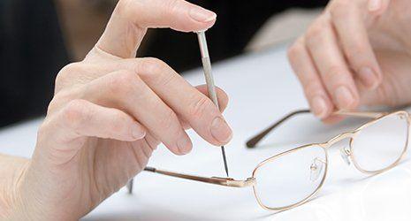 due mani che con un cacciavite di precisione avvitano le aste degli occhiali