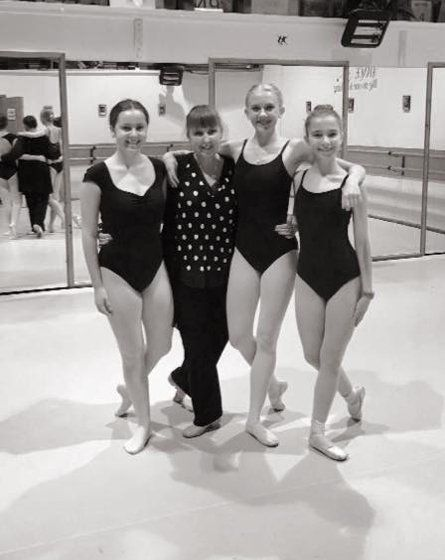 ballet dancers posing with the dance teacher