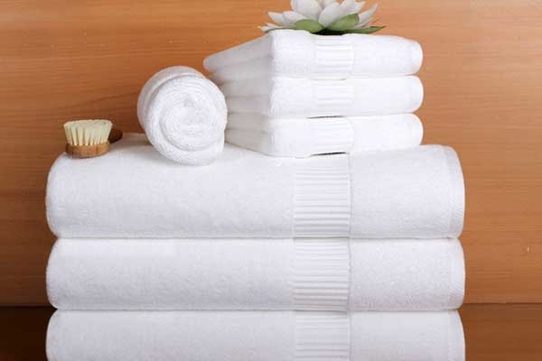 asciugamani piegati con sopr una spazzola e un fiore