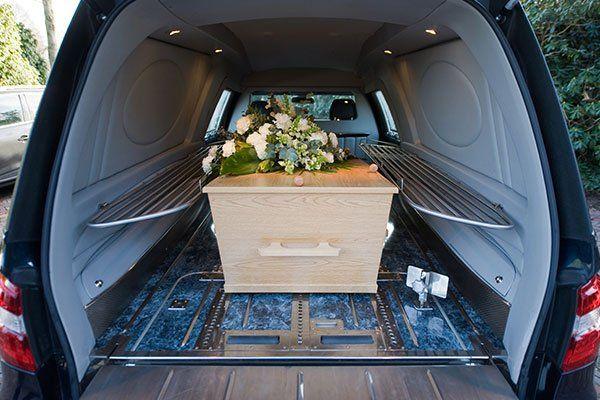 un carro funebre visto dal dietro con all'interno una bara in legno chiaro con sopra un bouquet di fiori