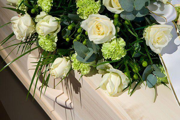 una bara in legno chiaro con sopra dei fiori bianchi