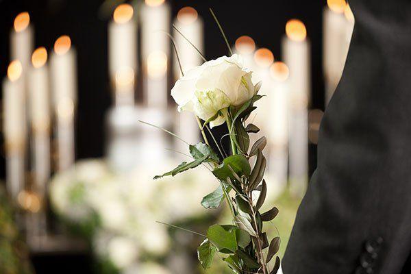 un braccio ci un uomo con un completo nero con una rosa bianca e dietro l'immagine sfuocata di alcune candele accese