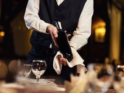 Sommelier mostrando una bottiglia di vino prima di aprirla