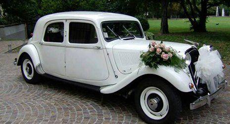 Vettura color bianco in un giardino con bouquet di fiori e velo da sposa