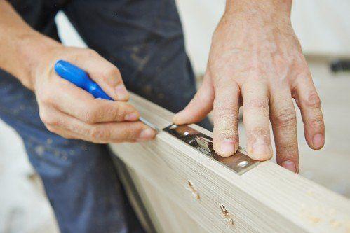 falegname che installa una serratura su una porta in legno