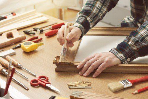 falegname che dipinge lo stipite di una porta in legno