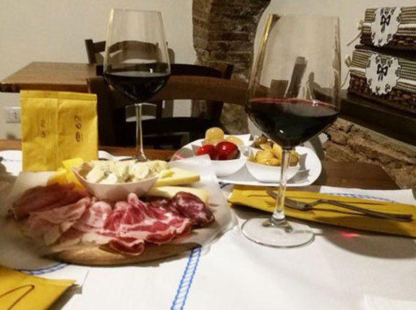 un tagliere con dei salumi, formaggi e due bicchieri di vino rosso