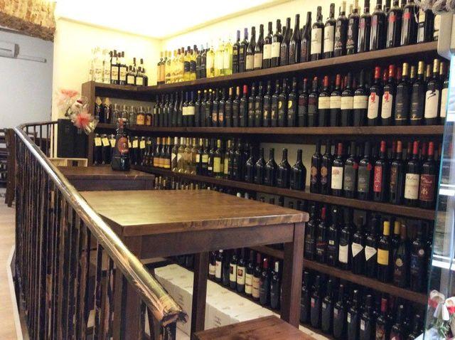 delle bottiglie di vino dentro a degli scaffali in un angolo enoteca