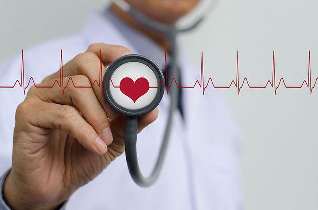 una mano che mostra uno stetoscopio con un disegno di un cuore