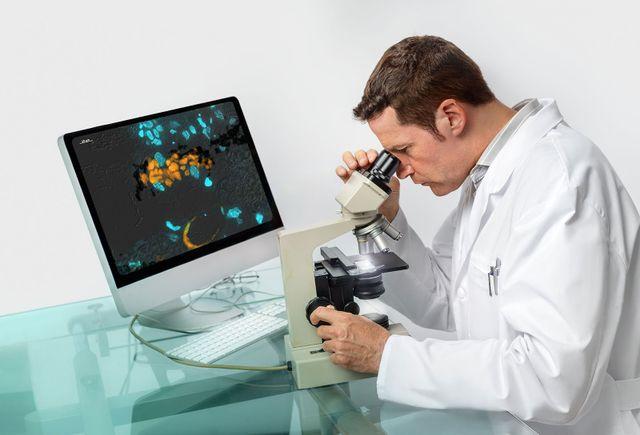 un dottore che guarda dentro un microscopio e di fronte un monitor sulla scrivania