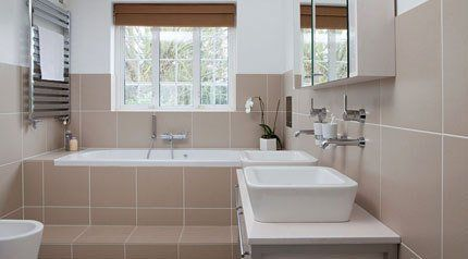 A bathroom with pale brown wall and floor tiles, and a bath set into a tiled surround