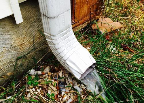 white gutter with rain coming out on grass