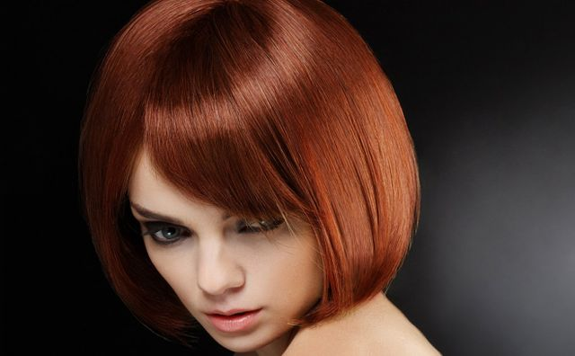 A lady with glossy red hair in a curly bob style