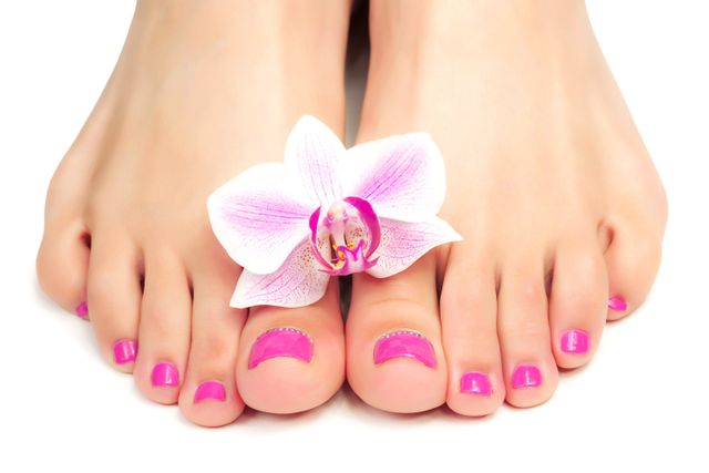Hands holding a yellow flower between feet, with matching French manicured nails