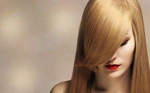 A lady with long shiny straight blonde hair with a long fringe over one eye