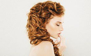 Profile of a lady with long side-swept curly golden brown hair