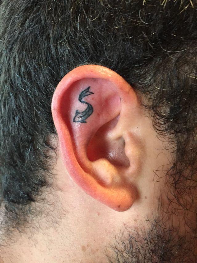 un tatuaggio di un pesce in un orecchio
