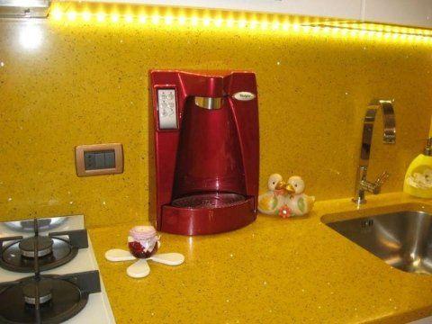 impianto di microfiltrazione rosso appoggiato vicino a un lavello e dei fornelli