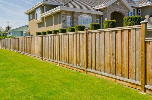 un recinto di legno con dietro una casa
