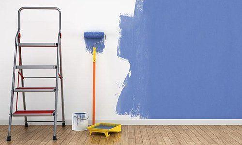 una scala, un rullo a manico e una parete in parte dipinta