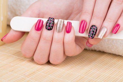una mano con delle unghie rosa e nere a disegni