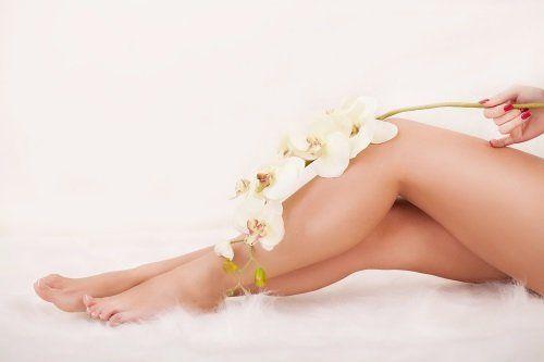 vista di due gambe di una donna e dei fiori bianchi