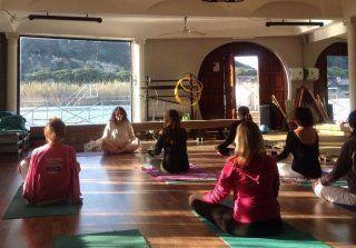 insegnante e studenti durante lezione yoga in una aula