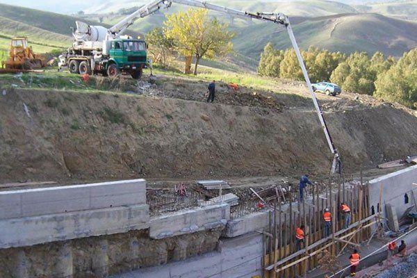 vista di un cantiere con degli operai con pettorine arancioni, su un ponteggio in legno e in alto un camion verde con una betoniera  e un lungo braccio meccanico grigio in uno scavo