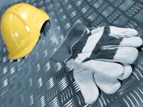 Un casco giallo con dei guanti da lavoro