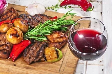 grigliata di carne con verdure e bicchiere di vino rosso