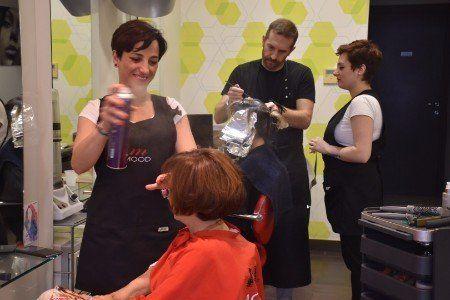 una parrucchiera che spruzza della lacca sui capelli di una signora