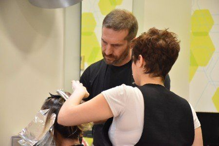 una parrucchiera e un parrucchiere al lavoro