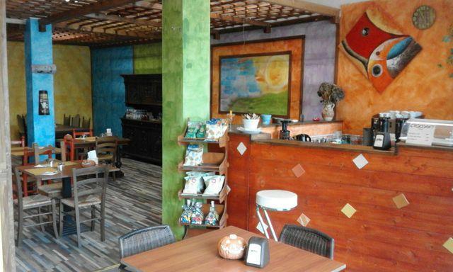 sala con un bancone bar e diversi tavoli con sedie