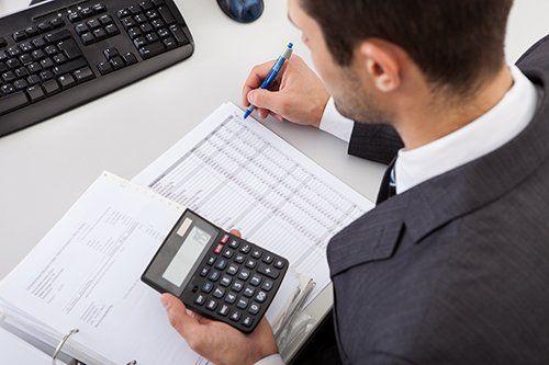 persona che scrive dei valori letti nella calcolatrice che tiene in mano