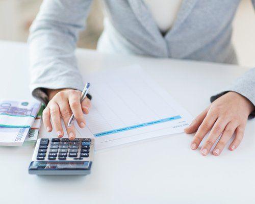 Una donna lavora su una calcolatrice con due mazzi di banconote a fianco