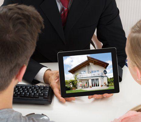 Consulente mostrando la foto di una casa ad una coppia