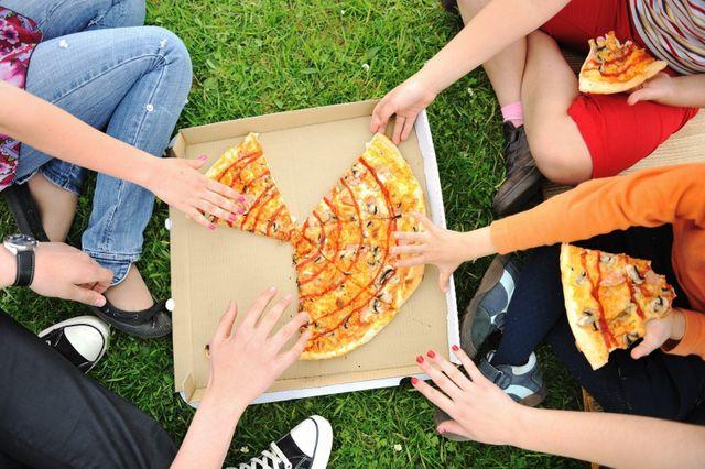ragazzi che mangiano una pizza seduti al parco
