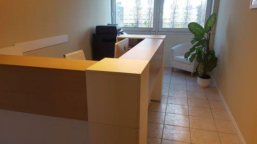 una scrivania in legno chiaro alta con divisorio, una poltrona bianca e un vaso con una pianta