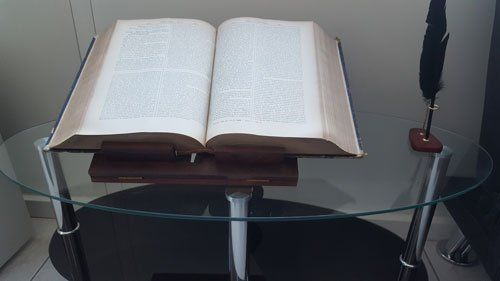 un tavolino di vetro con sopra un leggio in legno con un libro aperto