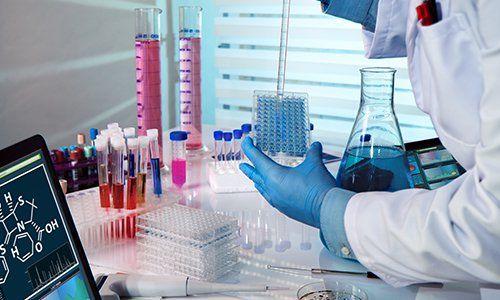 un uomo con un camice bianco in un laboratorio mentre fa degli esami