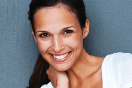 A smiling dark haired lady in a white top