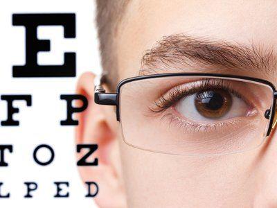 Dettaglio di un occhio di un ragazzo con occhiali e dietro la tabella di misurazione per la vista