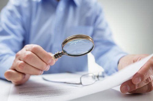 Man with magnifying glass and papers as symbol for FAQ