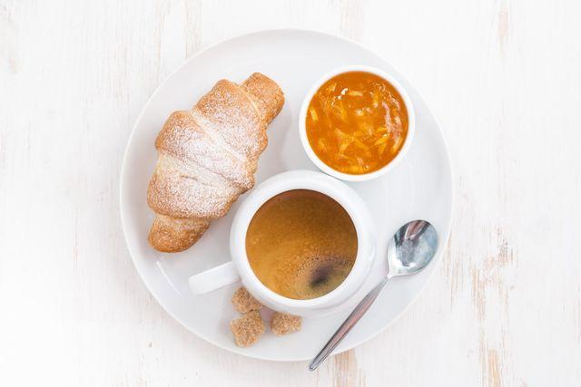 colazione con caffè nero, croissant e marmellata di arancia