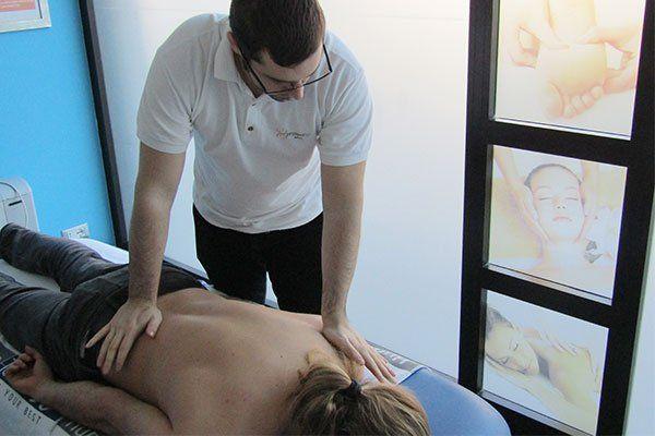 Un uomo con una maglia bianca mentre massaggia la schiena di una donna sdraiata su un lettino
