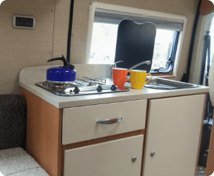 Sink and stove with a kettle on the stove and mugs next to it in a caravan