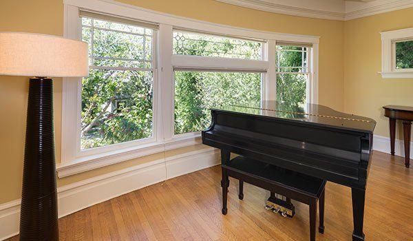 una stanza con parquet in legno, una lampada,una finestra e un pianoforte nero al centro - Bella Sicilia Traslochi e Trasporti - Caltanissetta