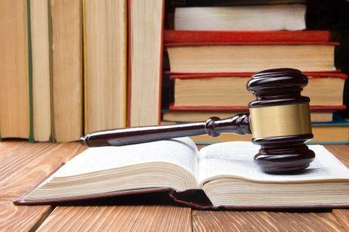 un martello di legno appoggiato su un libro aperto