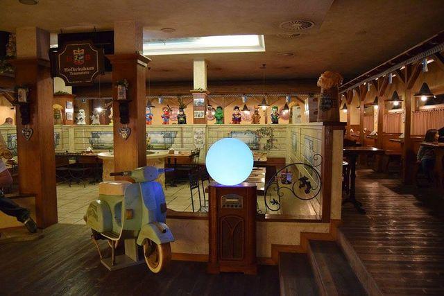 una Vespa, un tavolino con una lampada rotonda all'interno del ristorante